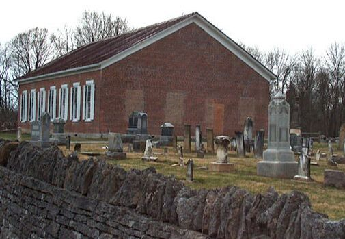 stone wall in the foreground, behind it is the cemetery, and behind that is the church building