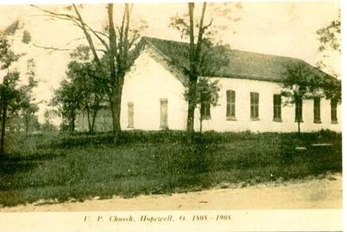 black and white photo of the church building from 1909 showing two sides of the exterior building, surrounded by trees