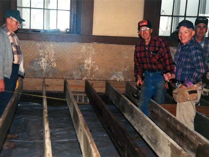 three men turn to smile at the camera after setting the planks in rows for the new pews